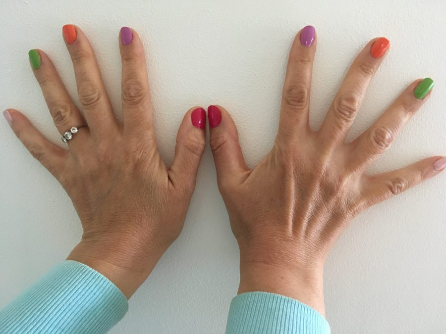 Hands with fingernails painted 5 different colours