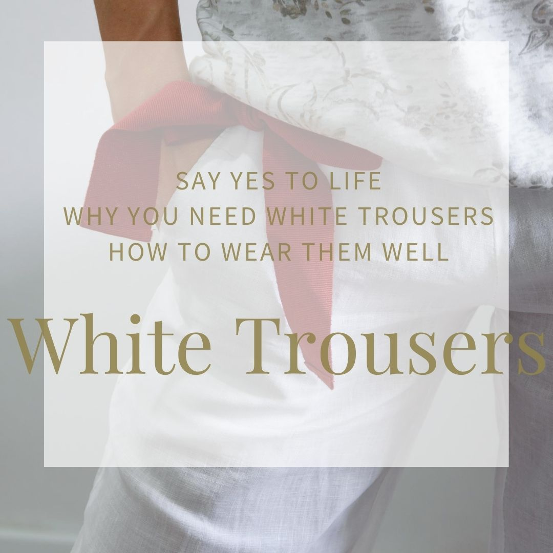 Waist view of white trousers worn with a red ribbon worn as a belt and tied in a bow at the side. Hand is in pocket. You can just see a pale, patterned top in white and beige. Relaxed, stylish summer look