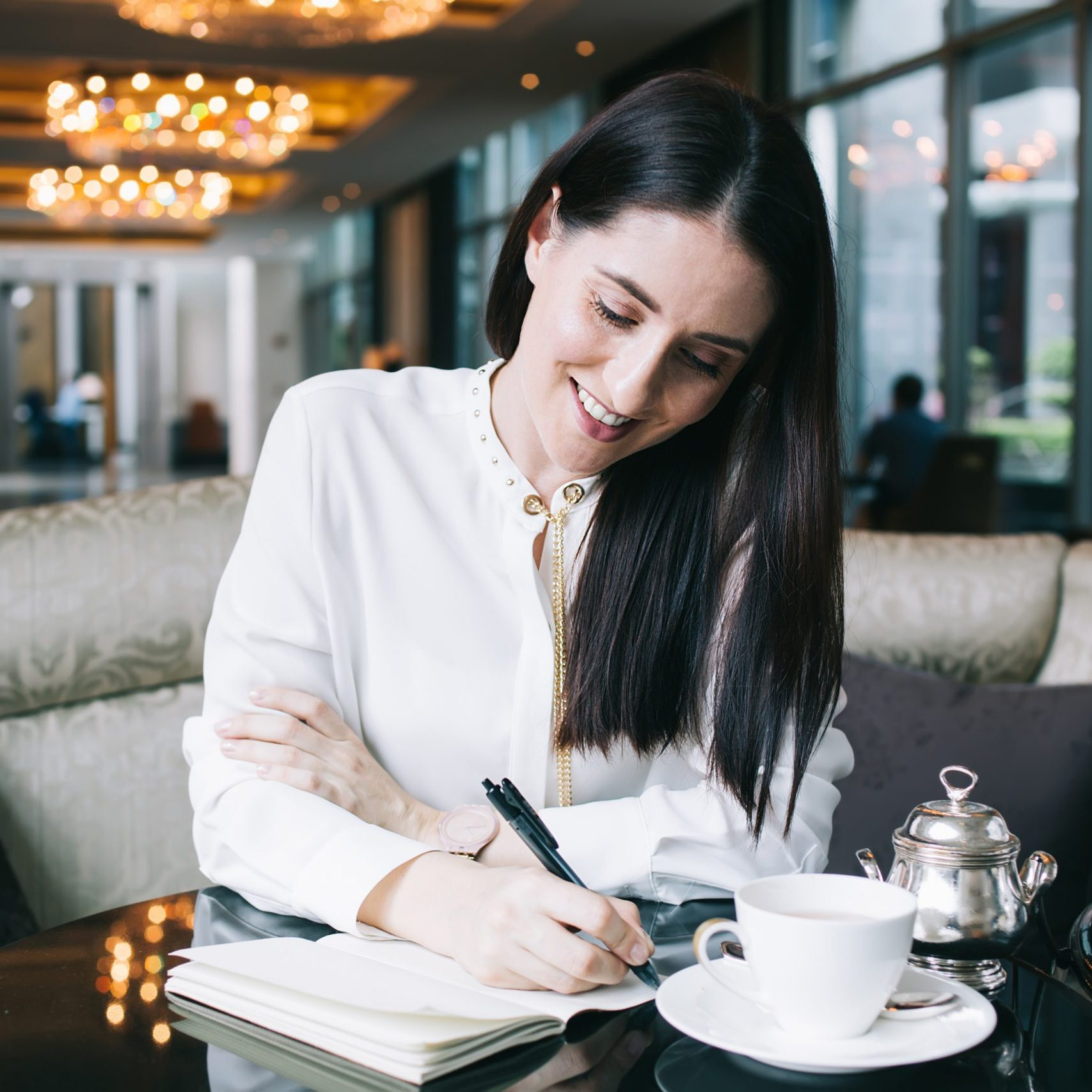 dark haired woman writing in her notebook, journalling, in a cafe, with a cup of tea