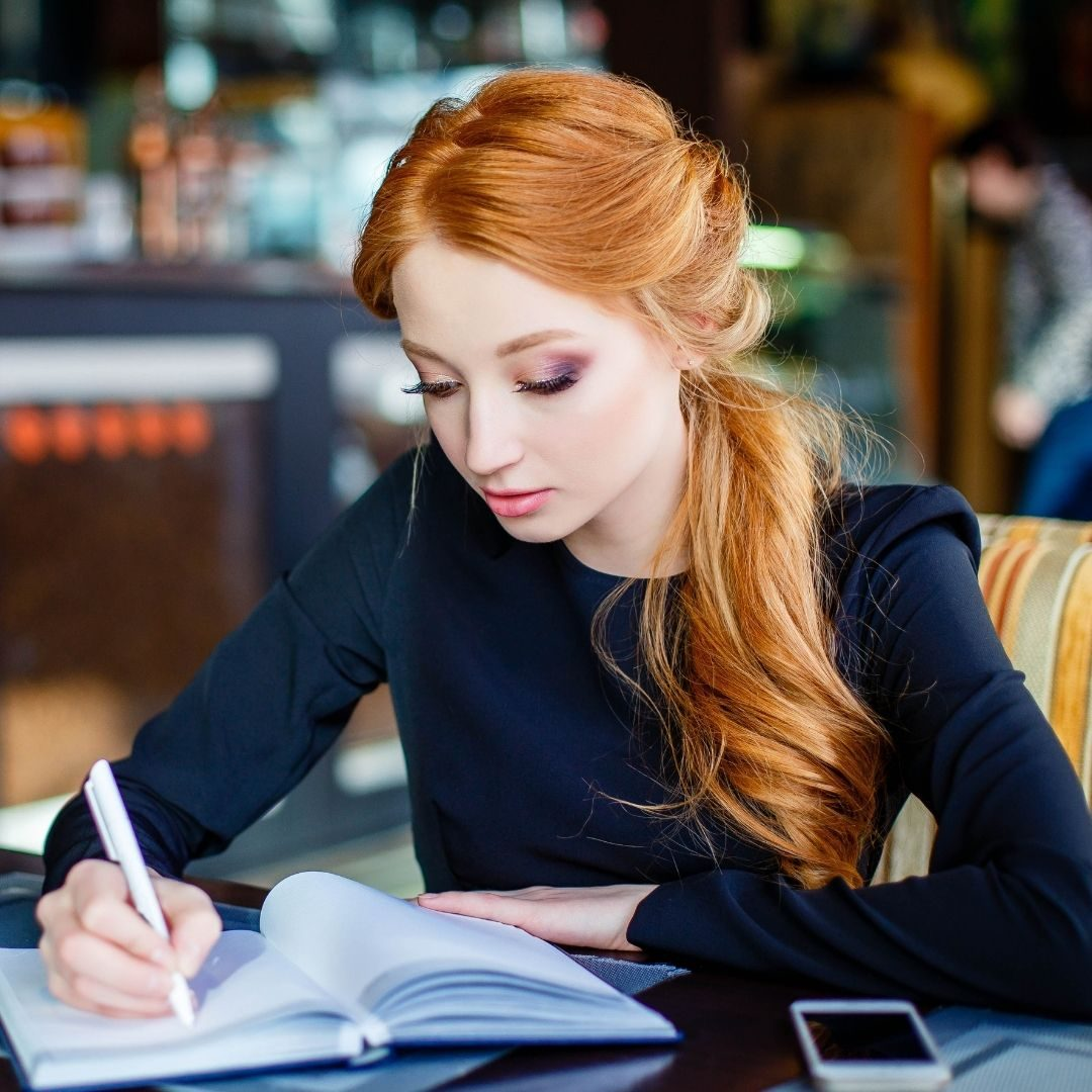 Copper haired woman in a blue dress sitting in a cafe writing in a notebook, journalling, working frocks