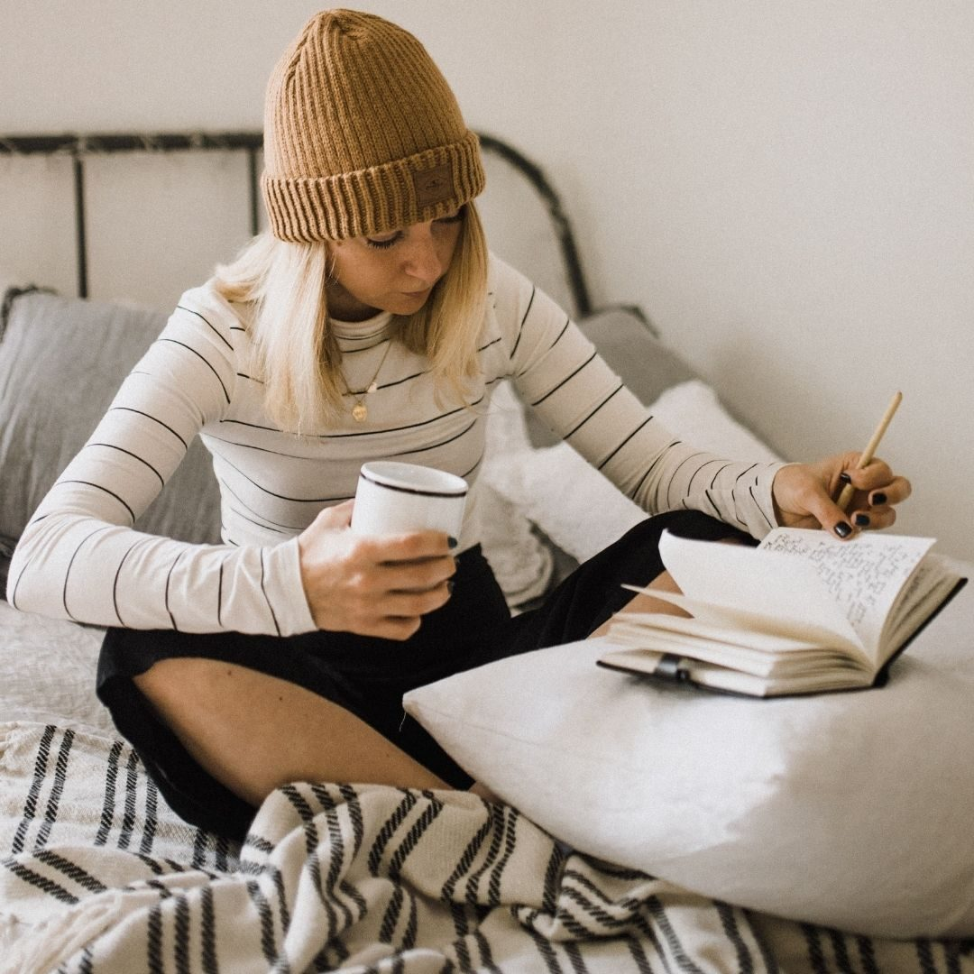 Woman in a beanie hat and striped jumper holding a coffee and writing in a notebook, journalling, working frocks